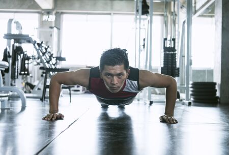 Sport. Young asian athletic man doing push-up muscular exercising in fitness gym.