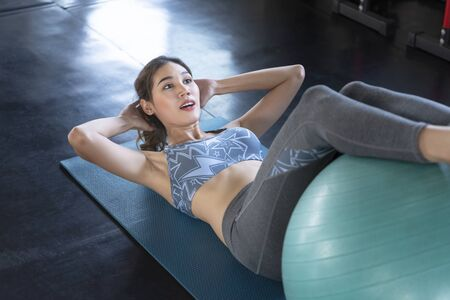 Asian women doing sit-ups exercise in fitness gym. healthy lifestyle.
