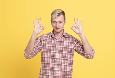 Portrait of a cheerful young man showing okay gesture looking at excellent isolated on the yellow background.