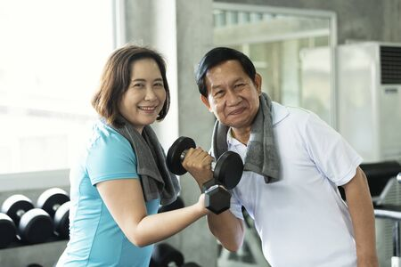 Asian senior man and woman exercise lifting dumbbell in fitness gym. elderly healthy lifestyle. Imagens