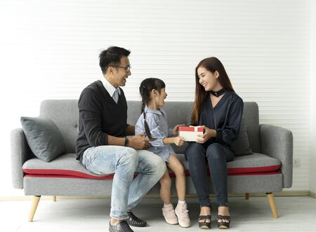 Asian daughter holding present with father and mother. concept surprise gift box for Birthday Day. Imagens