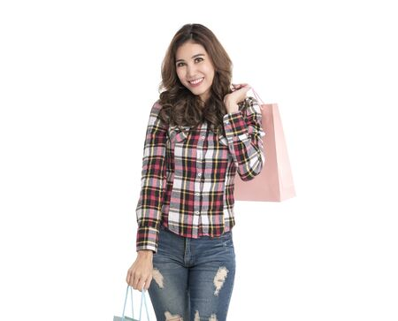 Portrait of an excited beautiful asian girl holding shopping bags isolated on white background.