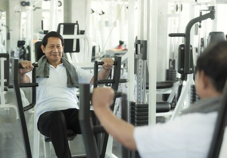 Asian senior man exercise lifting dumbbell in fitness gym. elderly healthy lifestyle.