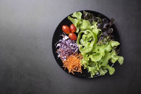 Fresh healthy vegetable salad with tomato, cucumber, spinach, lettuce in plate on table background. Imagens