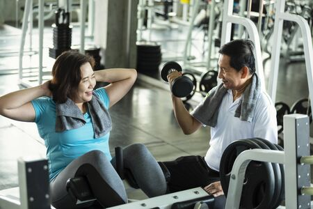 Asian senior man and woman exercise lifting dumbbell and sit up in fitness gym. elderly healthy lifestyle.