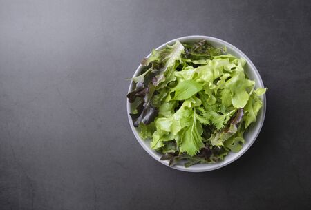 Fresh healthy vegetable salad with spinach, lettuce in plate on table background with free text space for diet menu.