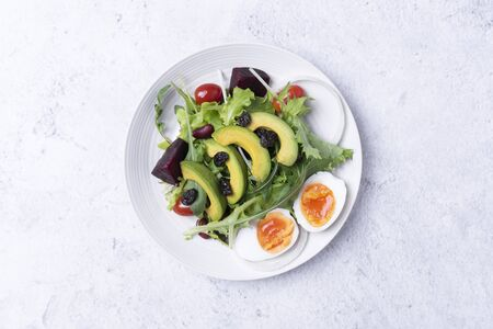 Fresh healthy vegetable salad with egg, tomato, avocado, spinach, lettuce in plate on table background.