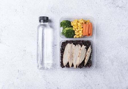 Fresh healthy diet lunch box with vegetable salad and water bottle on table background. Imagens