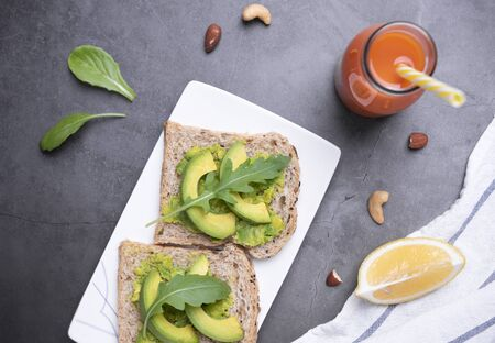 Fresh healthy avocado sandwich in plate with orange juice on table background. Imagens