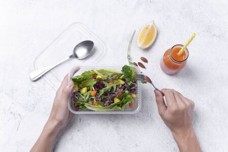 Hand holding fresh healthy diet lunch box with vegetable salad on table background.