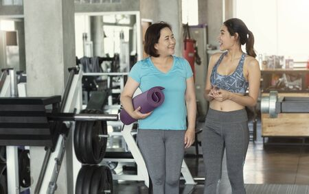 Happy asian couple senior and young woman holding yoga mats and walking in class of fitness gym.