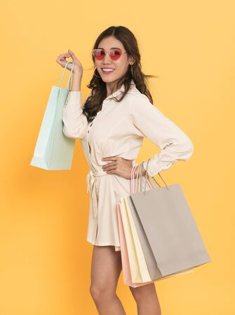 Portrait of an excited beautiful asian girl wearing dress and sunglasses holding shopping bags isolated on yellow background. 스톡 콘텐츠 - 130127351