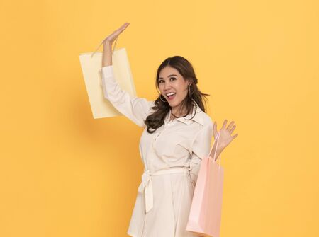 Portrait of an excited beautiful asian girl wearing dress holding shopping bags isolated on yellow background. 스톡 콘텐츠 - 130127397