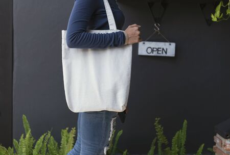 Girl is holding bag canvas fabric for mockup blank template on gray background.  global warming concept. 스톡 콘텐츠 - 130127814