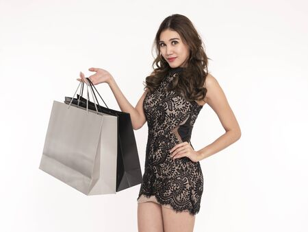 Portrait of an excited beautiful asian girl wearing dress and holding shopping bags isolated on white background.