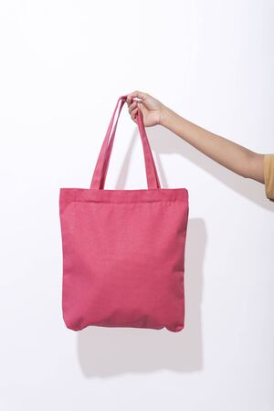 Girl is holding pink bag canvas fabric for mockup blank template on white background. global warming concept.