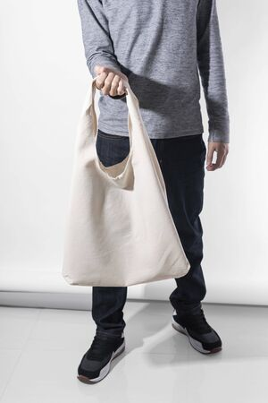 Man is holding bag canvas fabric for mockup blank template on white background. global warming concept. 스톡 콘텐츠