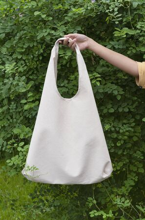 Girl is holding bag canvas fabric for mockup blank template on green nature background.  global warming concept. 스톡 콘텐츠