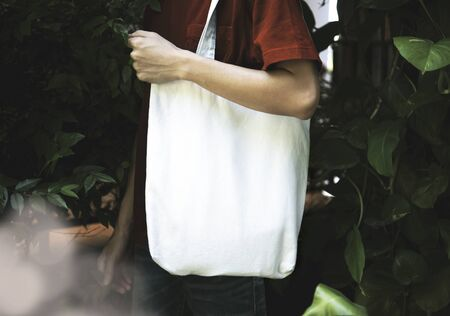 Man is holding bag canvas fabric for mockup blank template on nature background.  global warming concept.