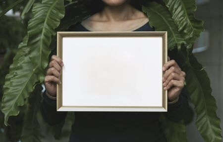 Hand Holding Blank Photo Frame for Design Mockup Template in the garden.
