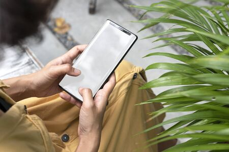 Mockup image of hands holding and using mobile phone with blank screen in garden.