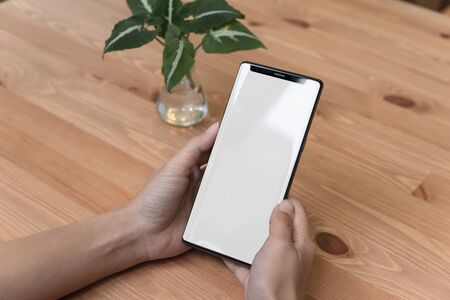 Mockup image of hands holding and using mobile phone with blank screen on wood table. Фото со стока
