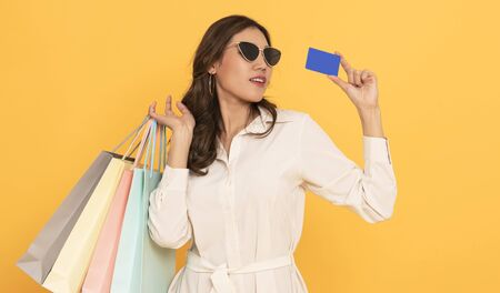 Portrait of an excited beautiful asian girl wearing dress and credit card holding shopping bags isolated on yellow background. 스톡 콘텐츠 - 130127440