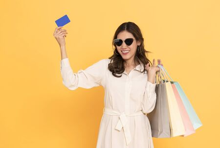 Portrait of an excited beautiful asian girl wearing dress and credit card holding shopping bags isolated on yellow background. 스톡 콘텐츠 - 130127441