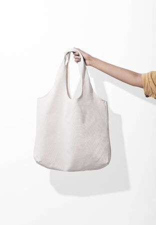 Girl is holding bag canvas fabric for mockup blank template on white background. global warming concept. Фото со стока