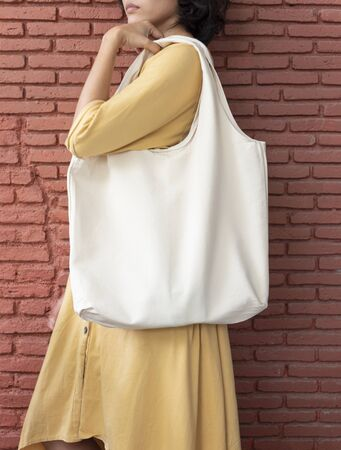 Girl is holding bag canvas fabric for mockup blank template on red wall background.  global warming concept. Фото со стока