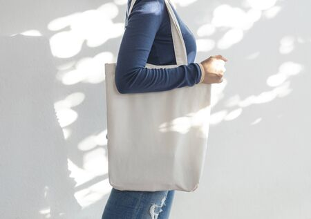 Girl is holding bag canvas fabric for mockup blank template on sunlight background.  global warming concept. Фото со стока