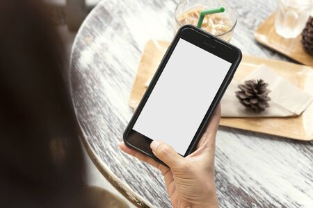 Mockup image of hands holding and using mobile phone with blank screen on wooden table in cafe. Фото со стока