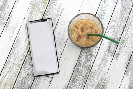 Mockup image of mobile phone with blank screen and coffee cup on wood table in cafe.