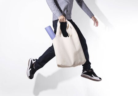 Man is jumping and holding bag canvas fabric for mockup blank template on white background. global warming concept.