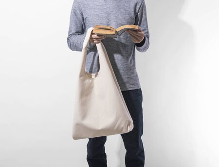 Man is holding bag canvas fabric for mockup blank template on white background. global warming concept. Фото со стока