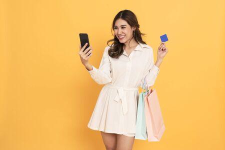Asiatische Frauen Shopper mit Handy und Kreditkarte für die Zahlung. Schwarzer Freitag und Online-Shopping-Konzept isoliert auf gelbem Hintergrund. Standard-Bild