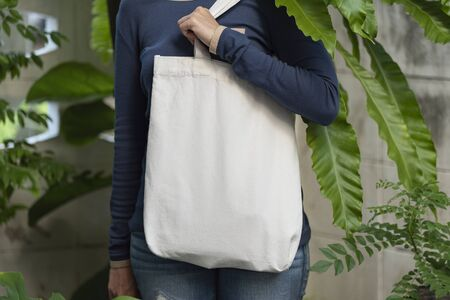 Girl is holding bag canvas fabric for mockup blank template on nature background.  global warming concept. Фото со стока
