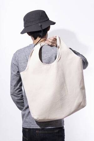 Man is holding bag canvas fabric for mockup blank template on white background. global warming concept. 스톡 콘텐츠 - 130127909