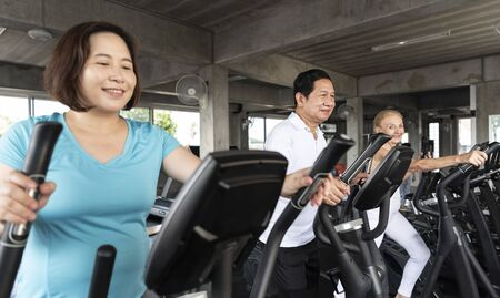 Group of senior exercise jogging at gym fitness smiling and happy. elderly healthy lifestyle. Foto de archivo - 130127450