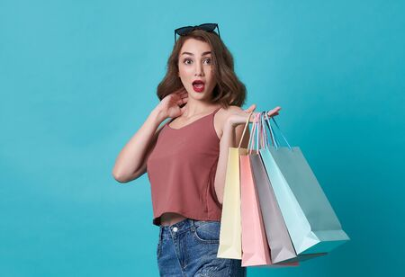 Portrait of an excited young woman hand holding shopping bag isolated over blue background.