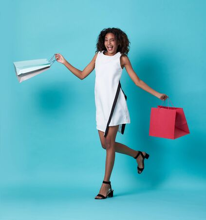 Happy beautiful young african woman in white dress and hand holding shopping bag jumping isolated over blue background.