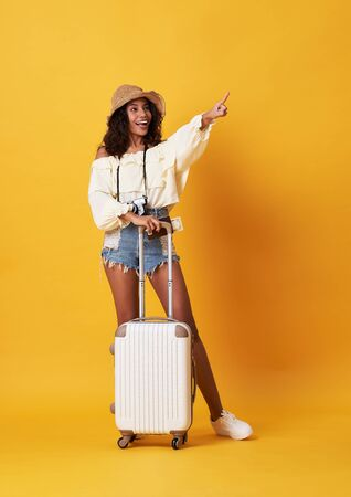 Cheerful young african woman dressed in summer clothes standing with a suitcase and pointing finger at copy space isolated over yellow background.