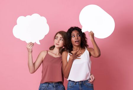 Portrait of two excited young woman holding blank speech bubble and make a face thinking on pink  background. 写真素材