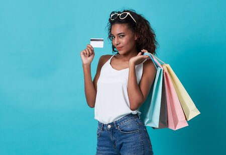 Portrait of a young african woman showing credit card and shopping bag isolated over blue background.