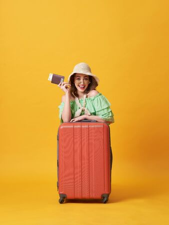 Cheerful young woman dressed in summer clothes holding passport with money while hug with suitcase isolated over yellow background.