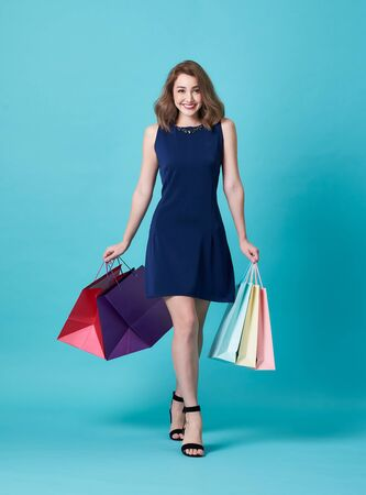 Happy beautiful young woman in blue dress and hand holding shopping bag isolated over blue background. 스톡 콘텐츠 - 130127540