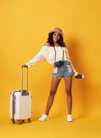 Cheerful young african woman dressed in summer clothes holding passport with money while standing with a suitcase isolated over yellow background.