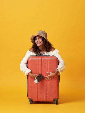 Cheerful young african woman dressed in summer clothes holding passport with money while hug with suitcase isolated over yellow background.
