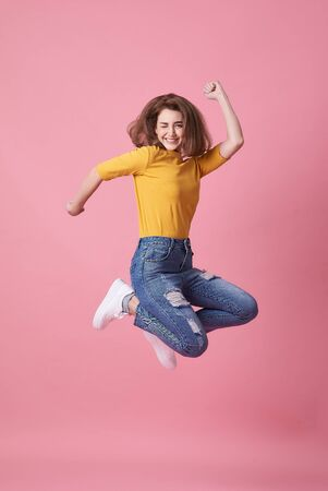 Portrait of a joyful young woman in yellow shirt jumping and celebrating over pink background.