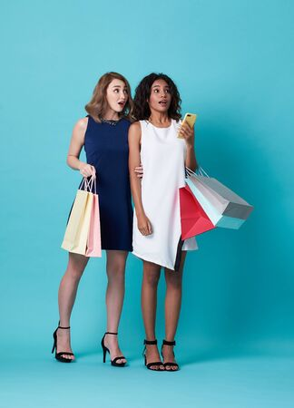 Portrait of two excited young woman hand holding shopping bag isolated over blue background.